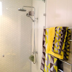 A feature wall of white hexagon ceramic tiles enlarges the shower space